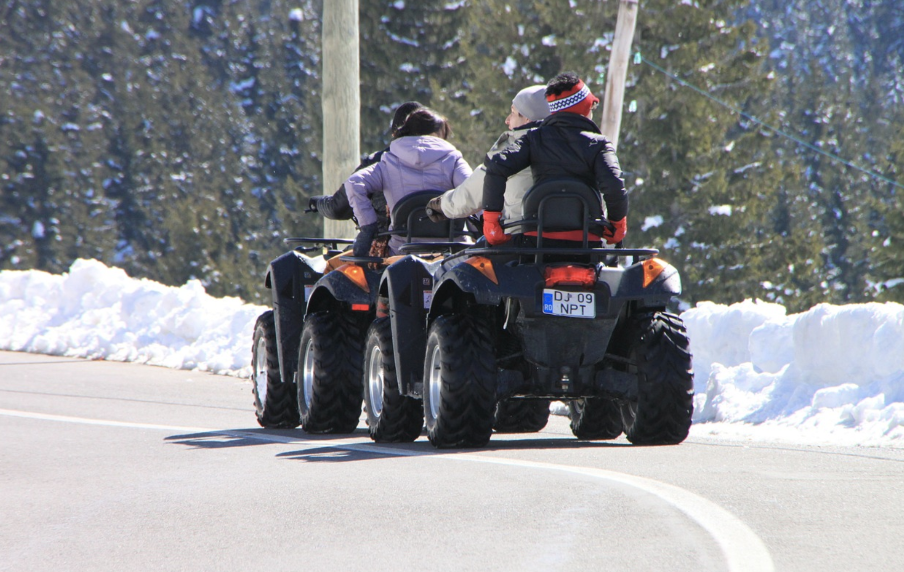 family riding an atv in the snow