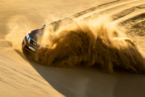 red nissan off road truck splashing the sand